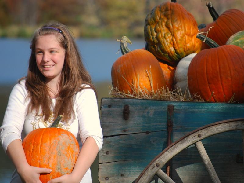 Girl by pumpkin wagon